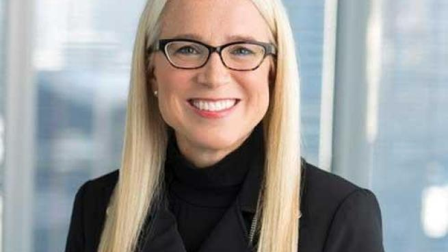 a woman wearing glasses and smiling at the camera
