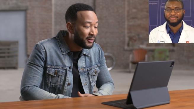 John Legend sitting at a table using a laptop computer