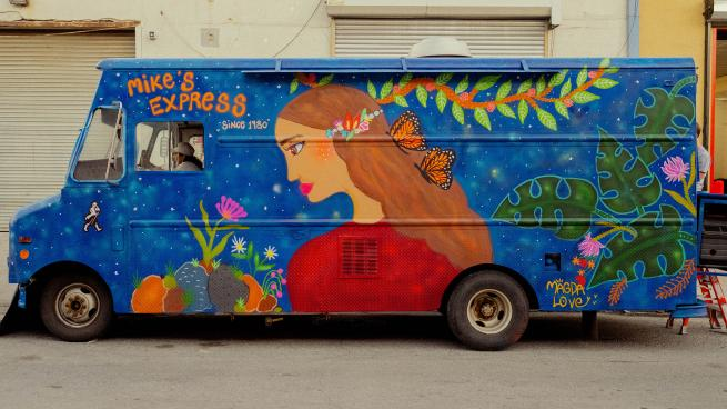 a colorful truck is parked on the side of a road