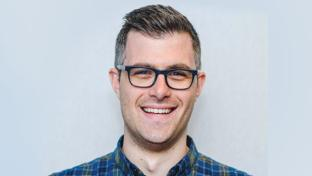 Daniel Ingram wearing glasses and smiling at the camera